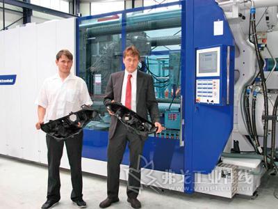 PLASTTECHNIK HOHLEBORN公司的技术经理Michael Ullrich和高级技术主管Gerald Ullrich手持用于欧宝Astra coupé车型上的头灯外壳部件,该大型部件由MacroPower 1000注塑机生产而出