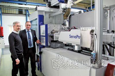 威克迈集团热固性产品经理Dipl.-Ing. Axel Neukirchen与威猛巴顿菲尔的销售Kai-Uwe Hilker站在一台用于加工热固性塑料的HM 150机器前