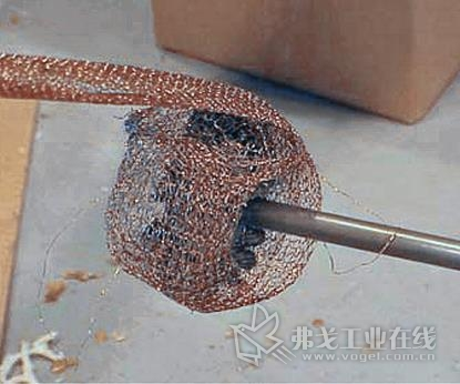 清洁机筒的第一步是在一根加长杆的末端将铜纱布绕在一把圆钢丝刷的外径上