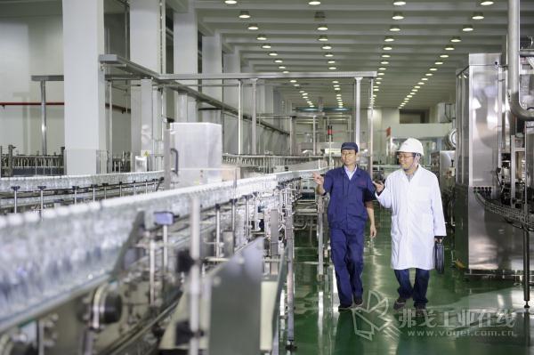 图1 西门子工程师与娃哈哈车间负责人巡视生产线