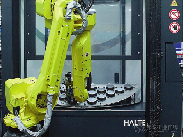 图 2 毛坯的供给和成品的下料都由回转工作台中的机器人来完成,加工 开始前它将毛坯从缓冲库托盘上拿起来、放入机床