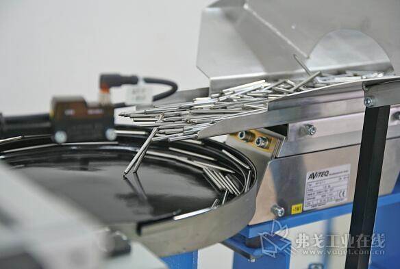 从一个储料仓里出来的金属柱螺栓首先到达一个螺旋输送机,目的是为了零件缓冲装置将工件纵向安置在一个线性的输送段上